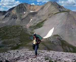 Woman standing on one of the peaks around Uncompahgre National Park with one of the Blue Lakes at her back