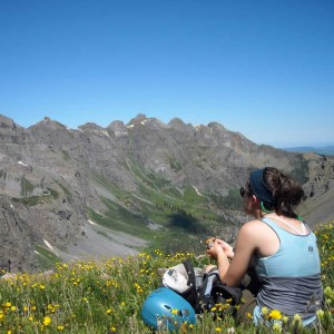 Woman in tank top, sitting on a yellow-flowered mountain meadow, overlooking several Telluride peaks.