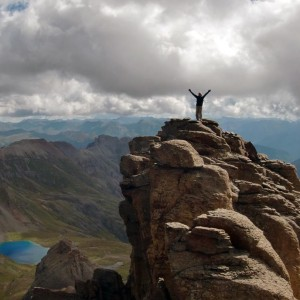 Man, with arms outstretched in victory, atop a rocky outcrop, with a small blue mountain lake in the distance below him.