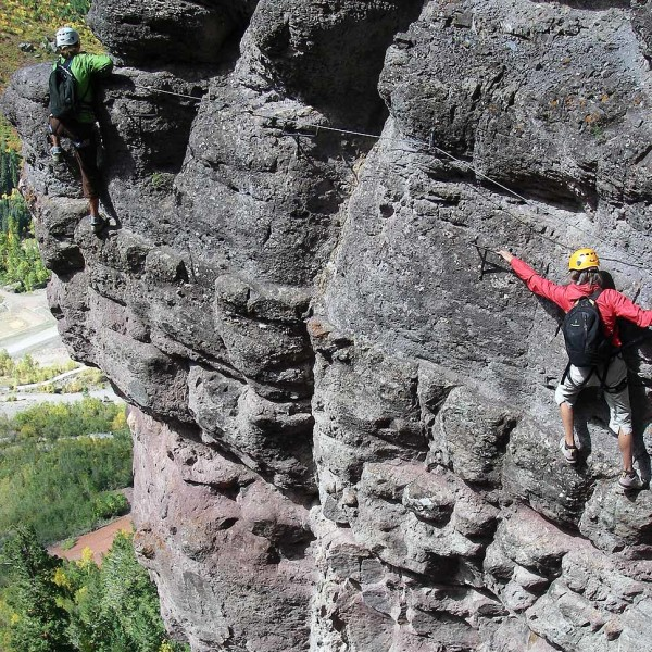 Two people moving sideways on the canyon wall using the steel cable and iron rungs of Telluride Via Ferrata, treetops far away below them.