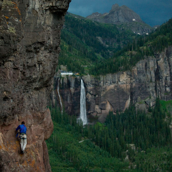 Man climbing Colorado Via Ferrata on foreground with magnificent falls in the background