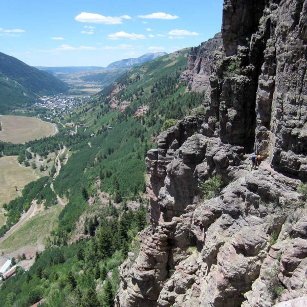 Man on Telluride Via Ferrata dwarfed by the canyon wall extending to the distance.
