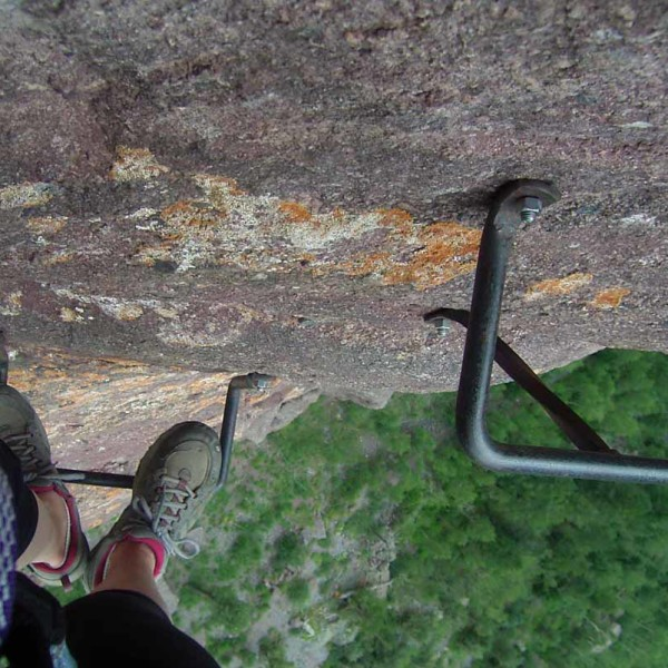 Looking down on someone's feet on the iron rungs of Co Via Ferrata