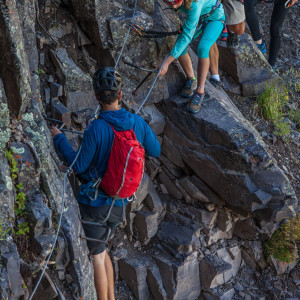Close shot of four people moving along the Telluride Via Ferrata on a canyon wall