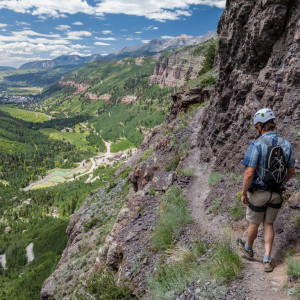 Man trudging on a narrow path along a Telluride Via Ferrata on a canyon wall overlooking a valley in the distance.